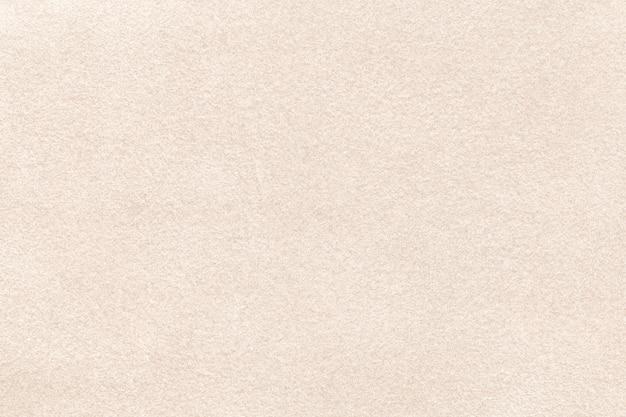 Sfondo opaco beige chiaro di tessuto scamosciato, primo piano. trama di velluto di tessuto color crema senza soluzione di continuità, macro. struttura del fondale in tela di feltro marrone.