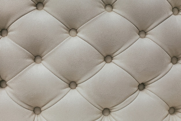 Motivo a rombi in tessuto velour beige chiaro con bottoni.