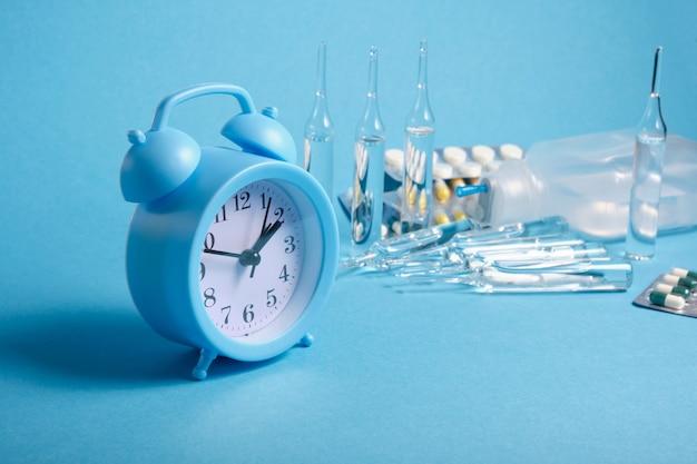 Sveglia azzurra e medicinali su sfondo blu, data di scadenza del concetto di farmaci