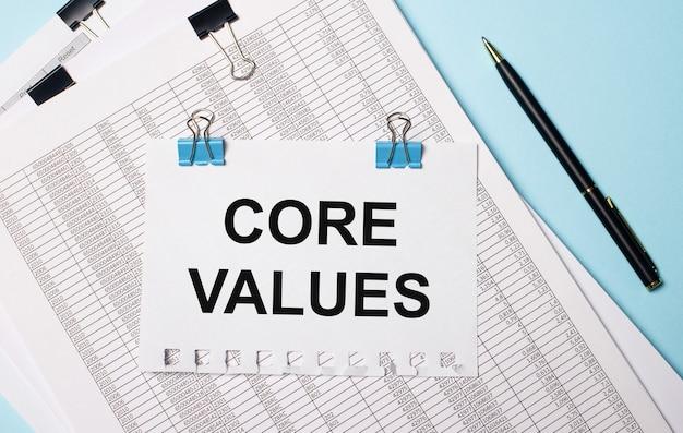 Su fondo azzurro, documenti, una penna e un foglio di carta su graffette blu con la scritta core values. concetto di affari.