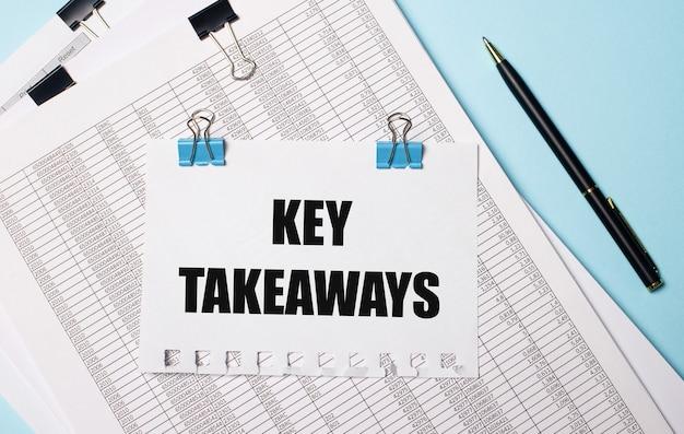 Su sfondo azzurro, documenti, una penna e un foglio di carta su graffette blu con la scritta key takeaways. concetto di affari.