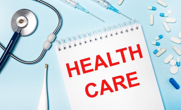 Su uno sfondo azzurro, un termometro elettronico, uno stetoscopio, pillole bianche e blu, siringhe e un quaderno con la scritta health care. concetto medico