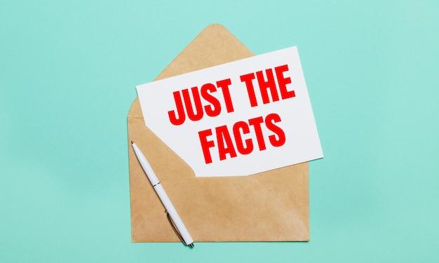 Su uno sfondo azzurro si trovano una busta artigianale aperta, una penna bianca e un foglio di carta bianco con il testo just the facts