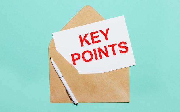 Su uno sfondo azzurro si trova una busta artigianale aperta, una penna bianca e un foglio di carta bianco con il testo punti chiave