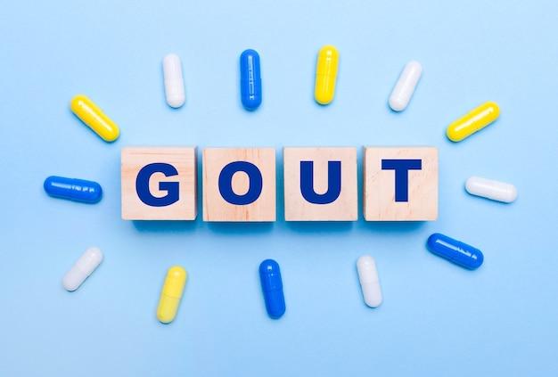 Su uno sfondo azzurro, pillole multicolori e cubi di legno con il testo gout. concetto medico