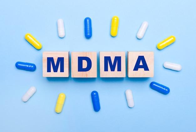 Su uno sfondo azzurro, pillole multicolori e cubi di legno con la scritta mdma. concetto medico
