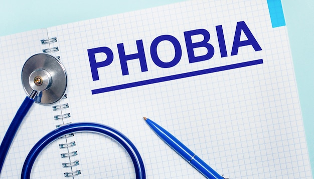 Su fondo azzurro un quaderno aperto con la scritta phobia, una penna blu e uno stetoscopio. vista dall'alto. concetto medico