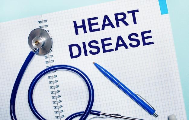 Su uno sfondo azzurro, un quaderno aperto con le parole heart disease, una penna blu e uno stetoscopio. vista dall'alto. concetto medico