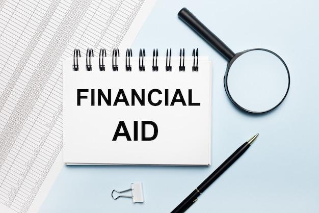 Su fondo azzurro, rapporti, una lente d'ingrandimento, una penna e un taccuino con la scritta aiuto finanziario