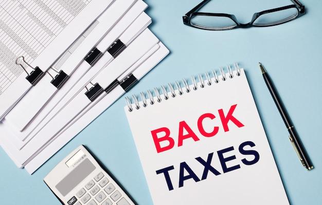 Su sfondo azzurro ci sono documenti, occhiali, una calcolatrice, una penna e un taccuino con la scritta back taxes. primo piano del posto di lavoro. concetto di affari