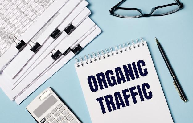 Su sfondo azzurro ci sono documenti, occhiali, una calcolatrice, una penna e un taccuino con la scritta traffico organico. primo piano del posto di lavoro. concetto di affari