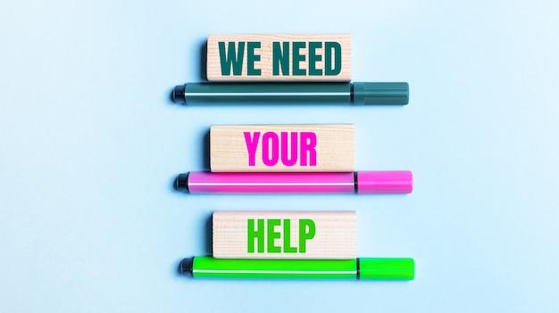 Su uno sfondo azzurro, ci sono tre pennarelli multicolori e blocchi di legno con la scritta we need your help