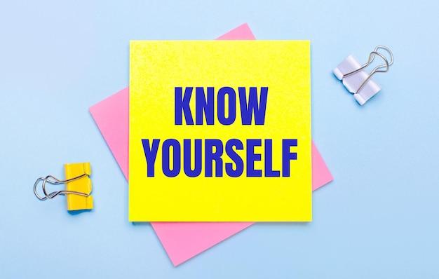 Su uno sfondo azzurro, ci sono graffette gialle e bianche, foglietti adesivi rosa e gialli con il testo conosci te stesso