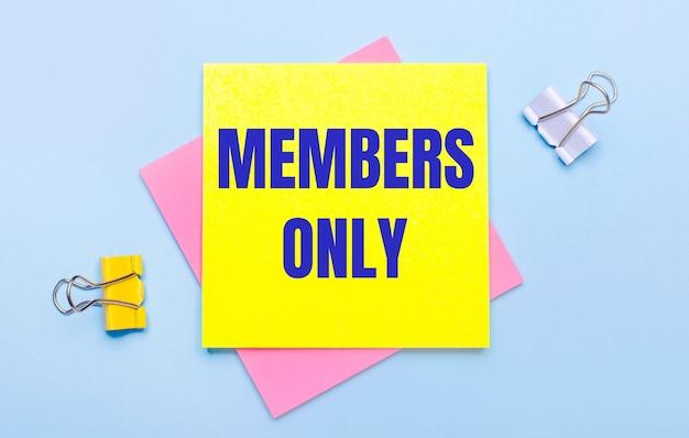 Su uno sfondo azzurro, ci sono graffette gialle e bianche, foglietti adesivi rosa e gialli con il testo solo per i membri