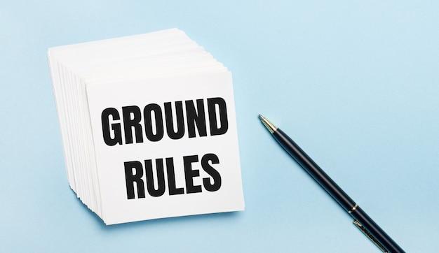 Su uno sfondo azzurro, c'è una penna nera e una risma di fogli di carta bianca con il testo regole di terra