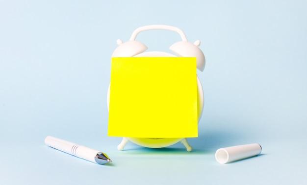 Su uno sfondo azzurro c'è una penna bianca e una sveglia con un adesivo giallo brillante incollato con un posto per inserire il testo. modello. copia spazio.