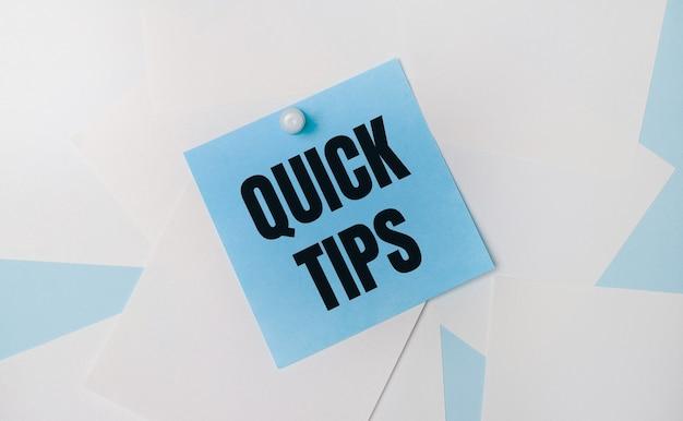 Su fondo azzurro, fogli quadrati bianchi. un adesivo quadrato azzurro con il testo quick tips è attaccato a loro usando una graffetta bianca.