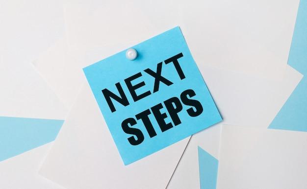 Su fondo azzurro, fogli quadrati bianchi. un adesivo quadrato azzurro con il testo next steps è attaccato a loro usando una graffetta bianca.
