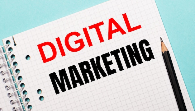 Su una superficie azzurra, un taccuino a scacchi con la scritta digital marketing e una matita nera