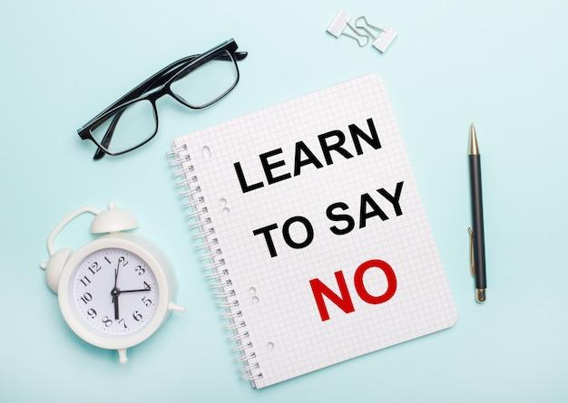 Su una superficie azzurra giacciono occhiali neri e una penna, una sveglia bianca, graffette bianche e un taccuino con le parole imparare a dire no. concetto di affari