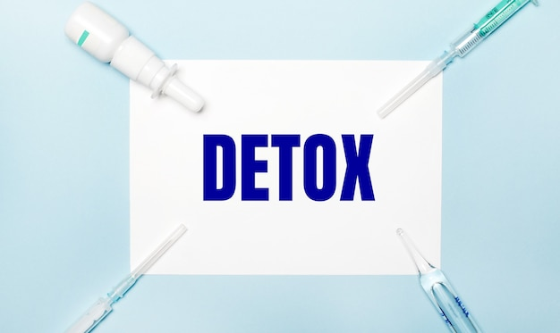 Su una superficie azzurra, siringhe, un flacone di medicinale, una fiala e un foglio di carta bianco con il testo detox. concetto medico