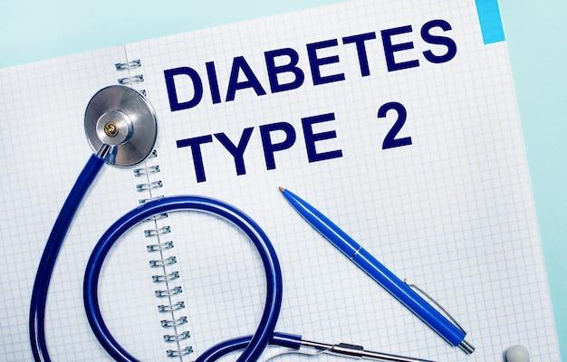 Su un tavolo azzurro, un taccuino aperto con le parole diabete tipo 2, una penna blu e uno stetoscopio. vista dall'alto. concetto medico