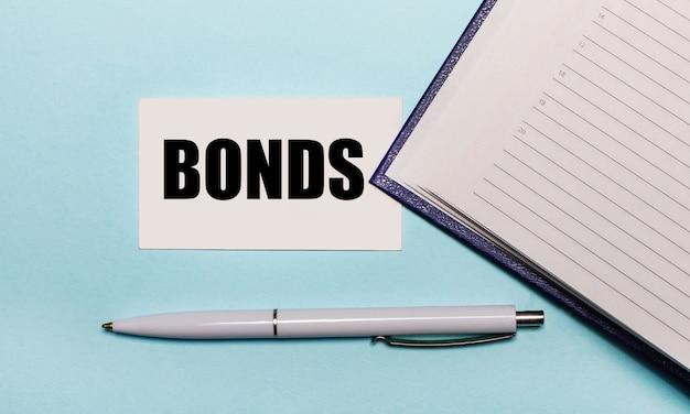 Su una parete azzurra, un taccuino aperto, una penna bianca e un biglietto con il testo bonds. vista dall'alto