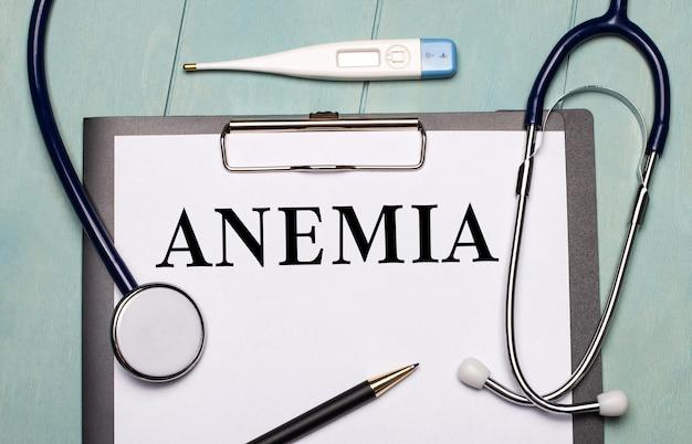Su una superficie di legno azzurra, c'è una carta con l'etichetta anemia, uno stetoscopio, un termometro elettronico e una penna. concetto medico.
