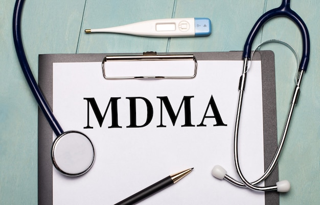 Su una superficie di legno azzurra, c'è una carta etichettata mdma, uno stetoscopio, un termometro elettronico e una penna. concetto medico
