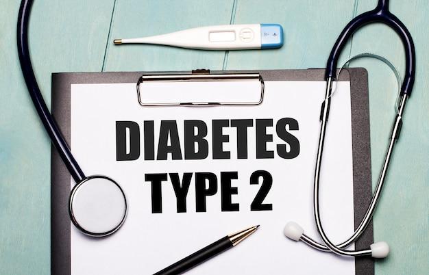 Su una parete di legno azzurra, c'è una carta etichettata diabete tipo 2, uno stetoscopio, un termometro elettronico e una penna. concetto medico