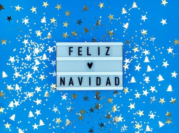 Scatola luminosa con frase feliz navidad, buon natale spagnolo con coriandoli.
