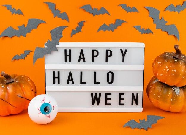 Scatola luminosa con frase happy halloween con zucche, pipistrelli e decorazione del bulbo oculare su uno sfondo arancione.