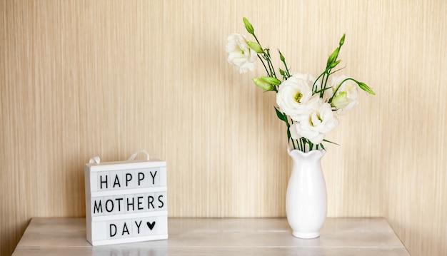 Scatola luminosa con scritte happy mother's day, fiori bianchi eustoma o lisianthus in vaso sulla tavola di legno con lo spazio della copia.