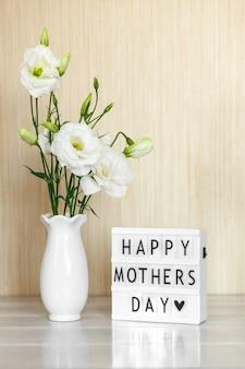 Scatola luminosa con scritta happy mother's day, fiori bianchi eustoma o lisianthus in vaso sul tavolo di legno.