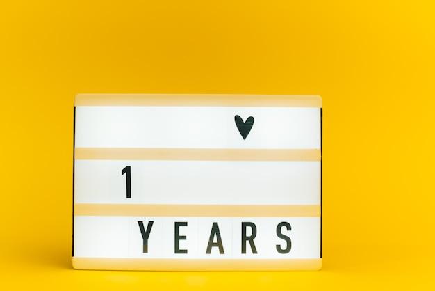 Scatola luminosa con testo, 1 anno, su muro giallo