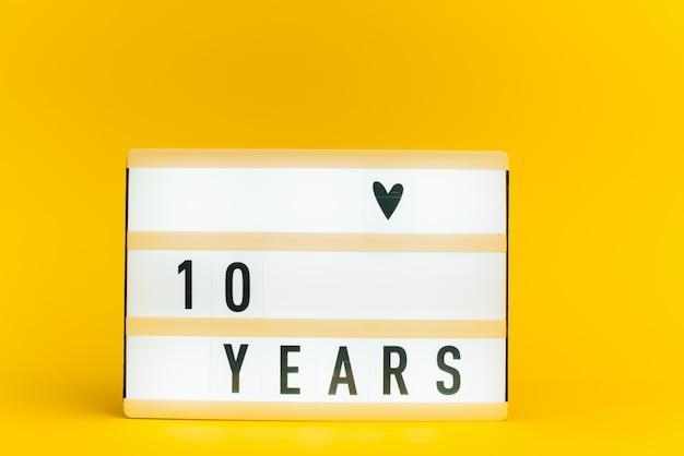 Scatola luminosa con testo, 10 anni, su muro giallo
