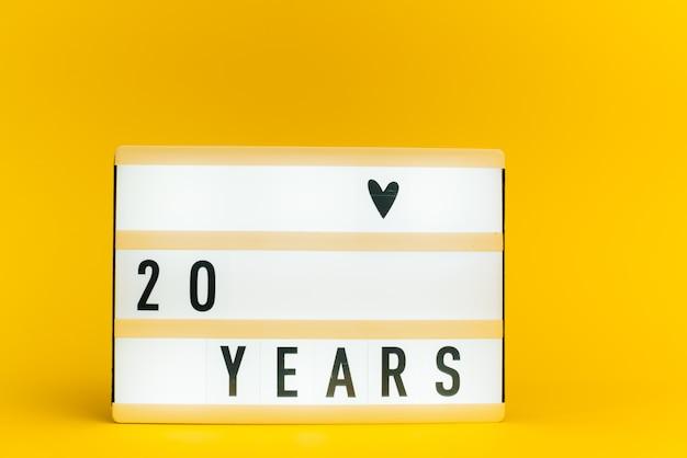 Scatola luminosa con testo, 20 anni, su muro giallo