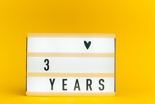 Scatola luminosa con testo, 3 anni, su muro giallo