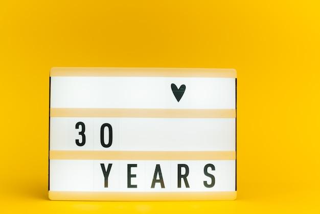 Scatola luminosa con testo, 30 anni, su parete gialla