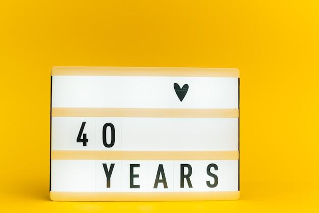 Scatola luminosa con testo, 40 anni, su muro giallo