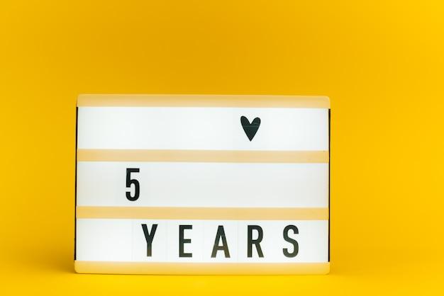 Scatola luminosa con testo, 5 anni, su muro giallo