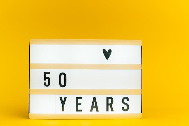 Scatola luminosa con testo, 50 anni, su parete gialla