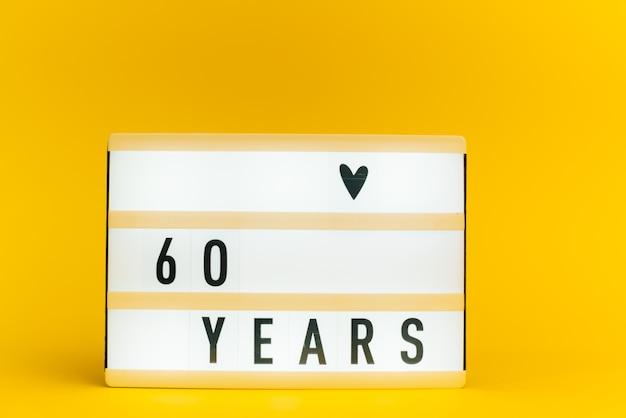 Scatola luminosa con testo, 60 anni, su muro giallo