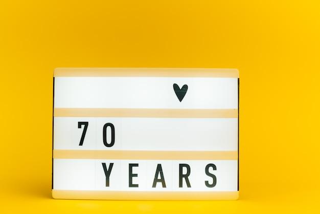 Scatola luminosa con testo, 70 anni, su parete gialla