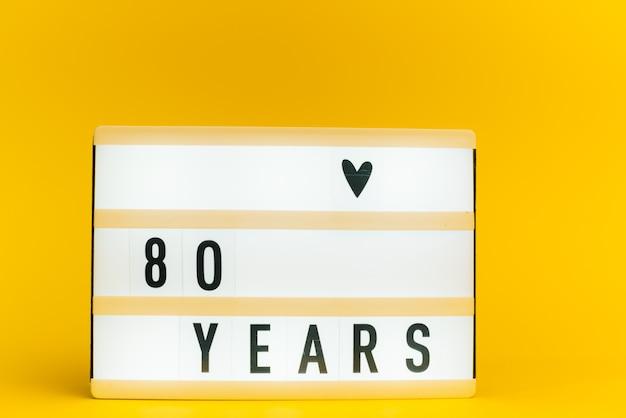 Scatola luminosa con testo, 80 anni, su parete gialla