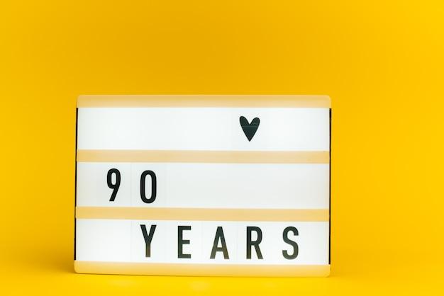 Scatola luminosa con testo, 90 anni, su muro giallo