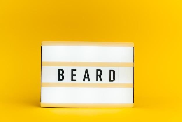 Scatola luminosa con testo, beard, sulla parete gialla