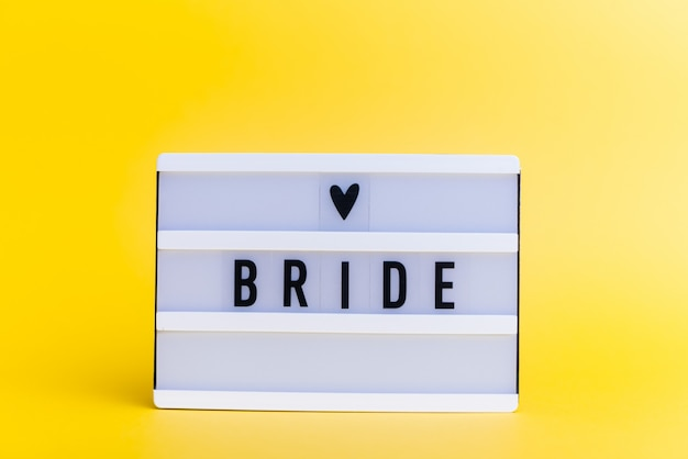 Scatola luminosa con testo, sposa, sulla parete gialla