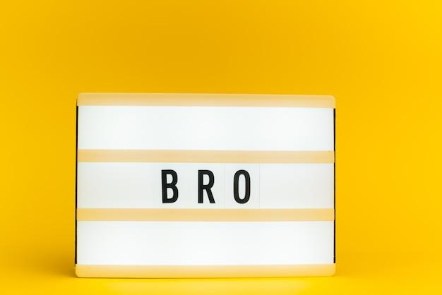 Scatola luminosa con testo, bro, sulla parete gialla