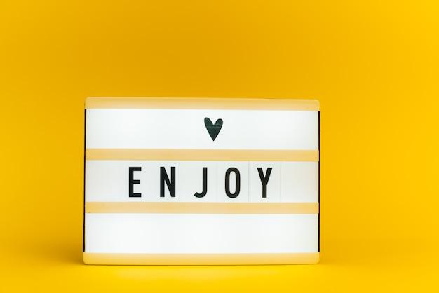 Scatola luminosa con testo, enjoy, sulla parete gialla